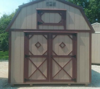 Lofted storage barn with brown sides and red trim